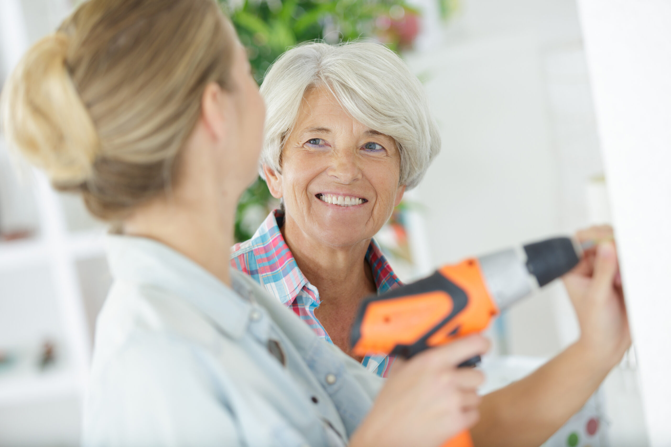 smiling mother and daughter working on home upgrades