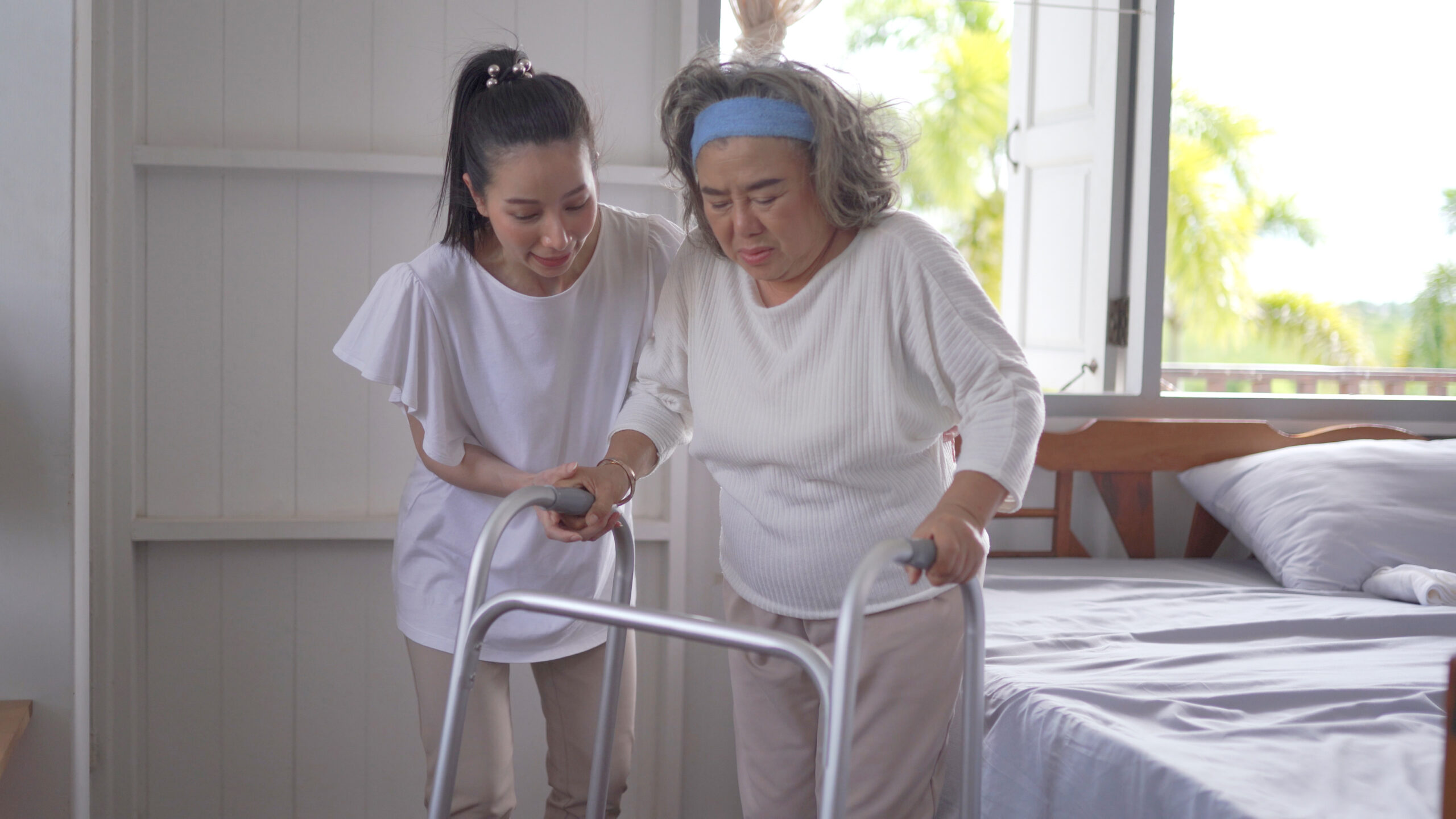 Adult daughter family caregiver supporting senior mother using a walker at home