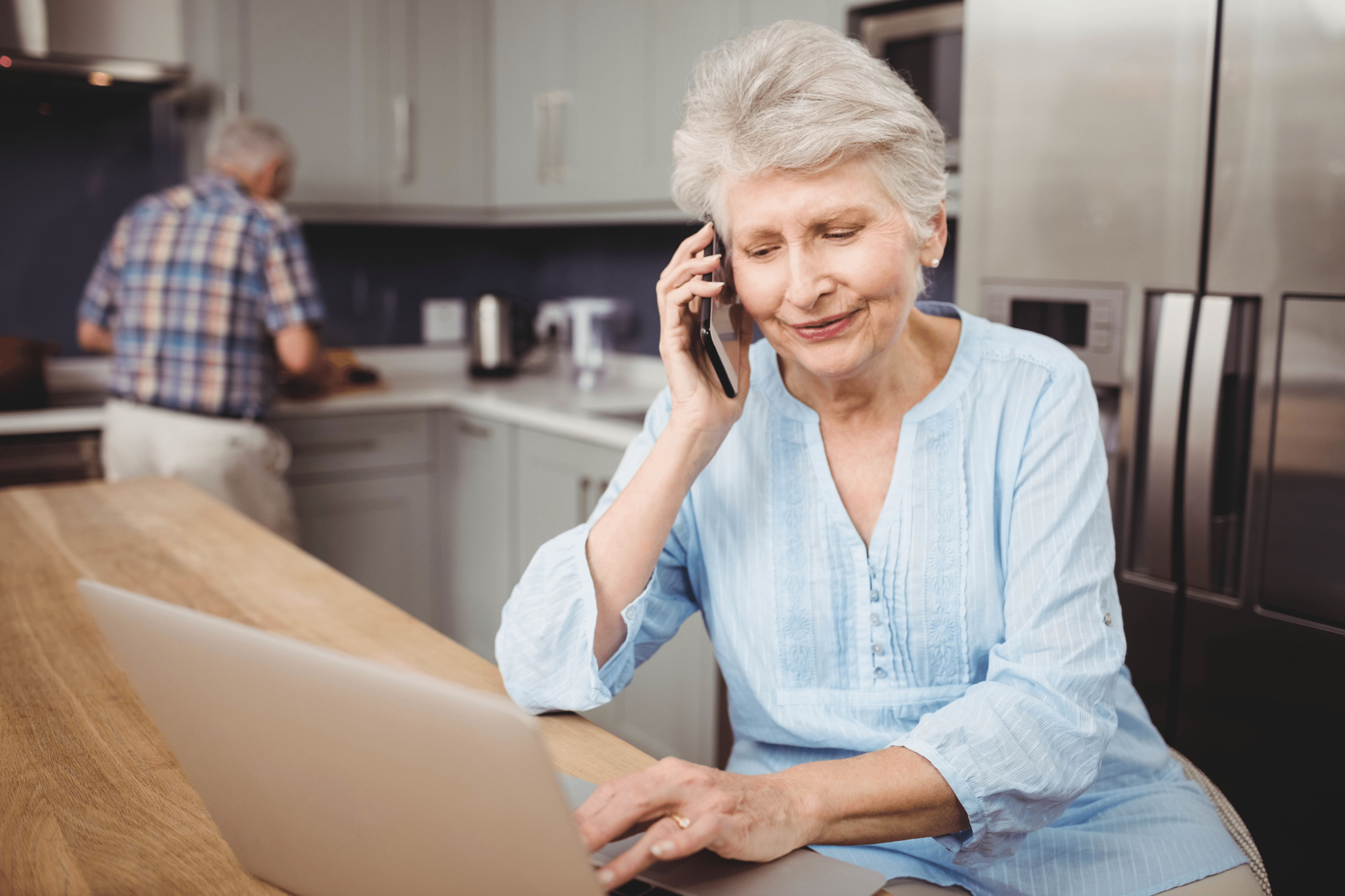 Older woman on the phone looking at her laptop