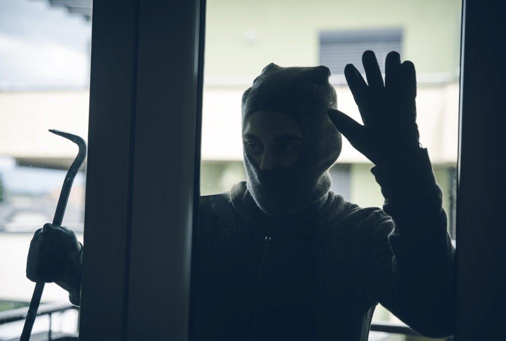 burglar looking into window home security for seniors